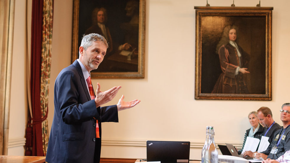 Martyn Percy speaking with oil paintings hanging behind hiim