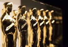 A series of gold Oscar statues on display.