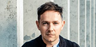 Iestyn Davies sits in front of a grey wall