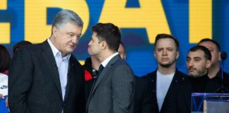 The image shows Petro Poroshenko and Vladimir Zelensky engaging in a debate on the 19th of April 2019. They are in front of a blue background.