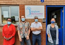 Four adults wearing masks in front of Asylum Welcome. From left to right: Caritas Umulisa, Simon Dawson, Almas Farzi ('Navid'), Helena Cullen