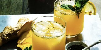 Two orange drinks sit in sunlight, surrounded by ingredients