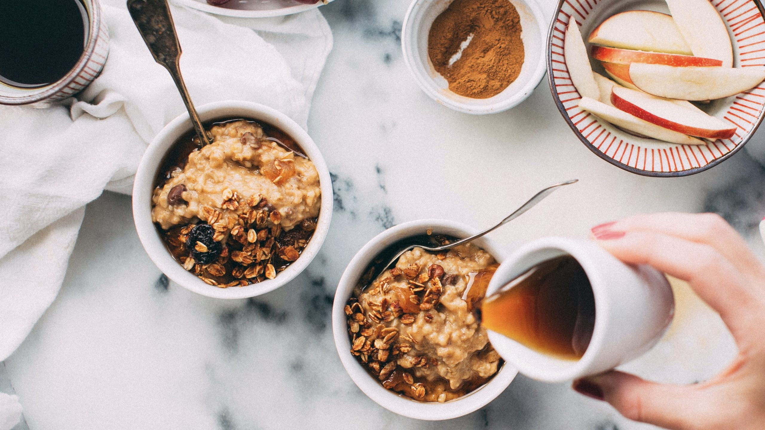 Syrup is poured over bowl of overnight oats at a breakfast set up (coffee, apple slices)