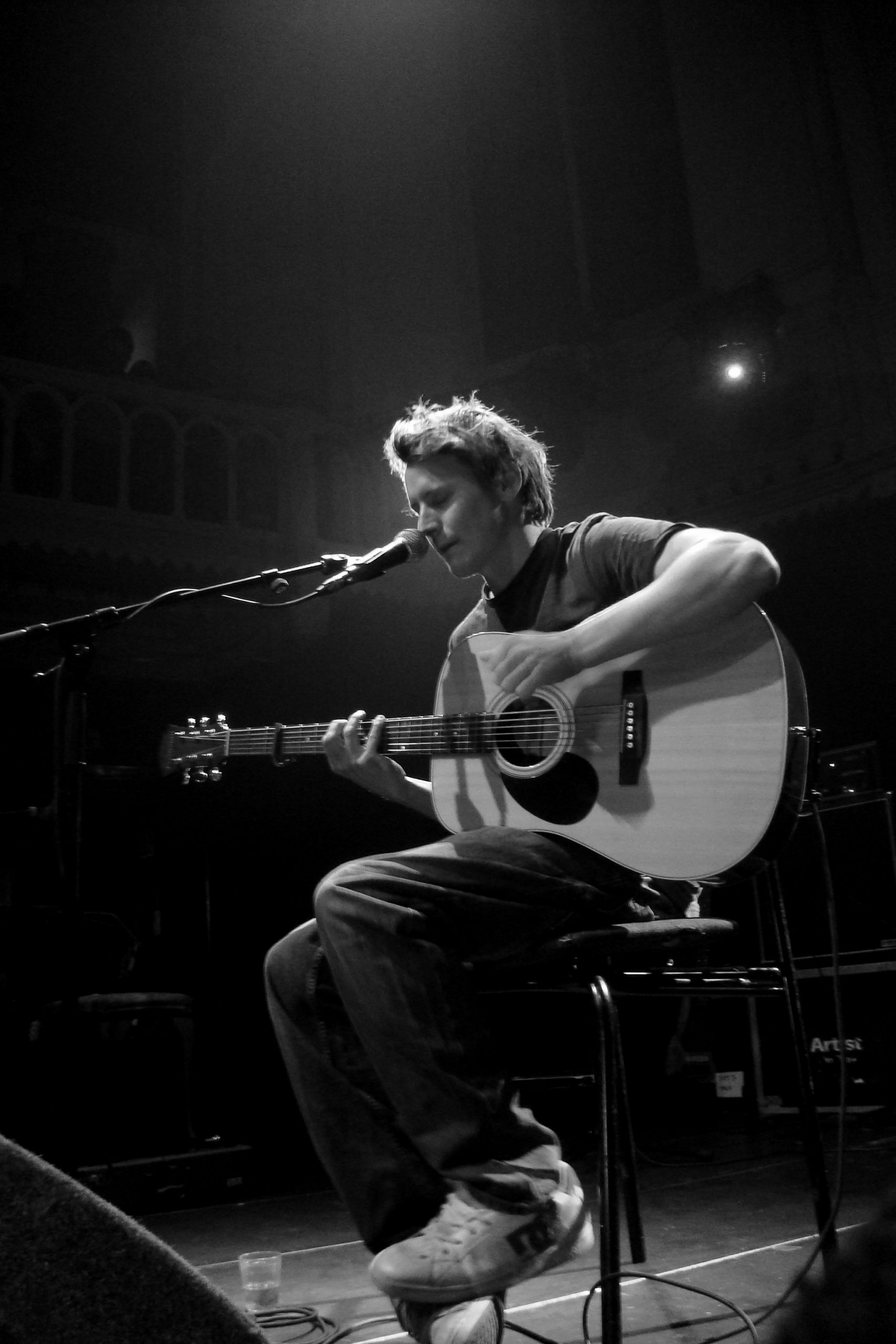 Ben Howard performing at Paradiso, Amsterdam, singing and playing the acoustic guitar whilst seated.