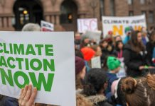 """A sign saying """"CLIMATE ACTION NOW"""" on the left, with protestors in the background."""