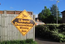 """A diamond-shaped yellow sign saying """"Liberal Democrats Winning Here"""" attached to a wooden fence."""