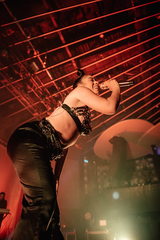 Kali Uchis sings at the Rebel Night Club for the 'In Your Dreams Tour'. She is wearing a leather bra and satin trousers.