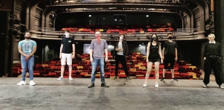 Seven people standing on a stage, facing away from an empty audience, whilst wearing masks.