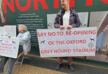 """A man holding a white sign with red writing saying: """"SAY NO TO RE-OPENING OF THE OXFORD GREYHOUND STADIUM"""""""