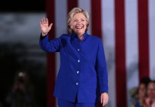 Hillary Clinton in a blue suit waving